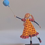 Art doll grasping string of balloon