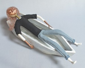 art doll Current Drift reclines in her small wooden boat