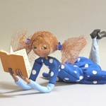 reclining art doll figure with book