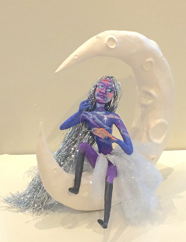 Weaving Dreams celestially colored art doll seated on the crescent moon