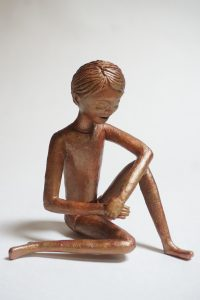 Seated figure with faux bronze finish