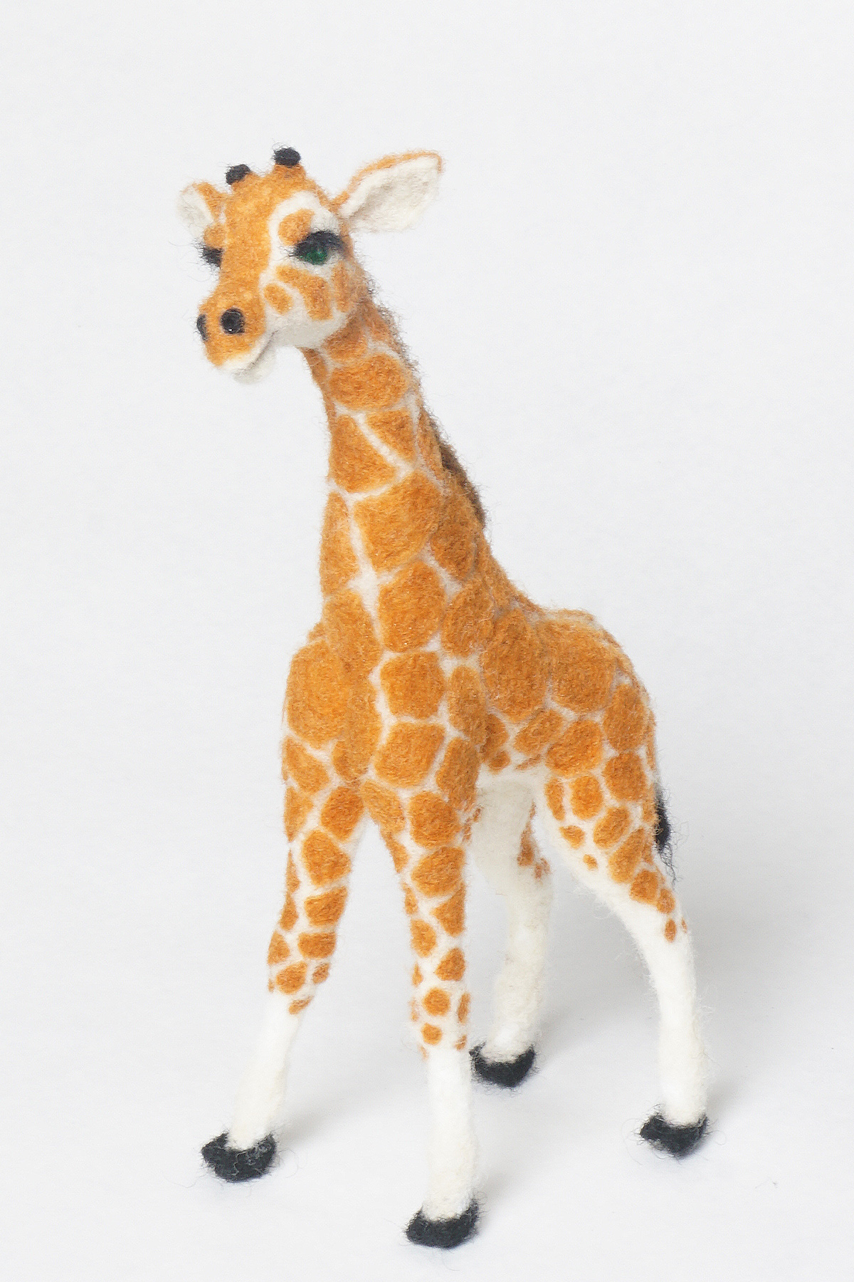 needle felted baby giraffe before her bow and ID bracelet accessories