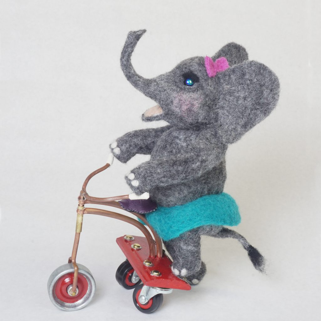 """""""Roll"""" anthropomorphic elephant art doll sculpture on handcrafted steampunk push tricycle. Needle felted wool figure."""